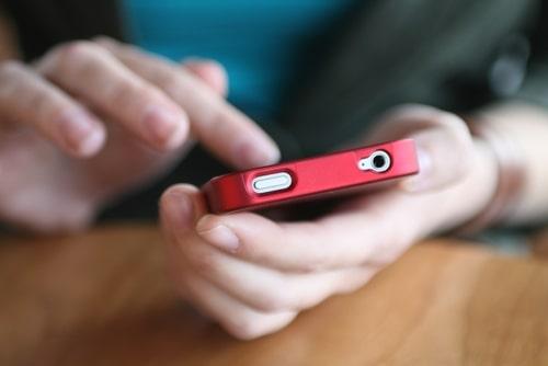 女性がカフェで携帯を操作している様子