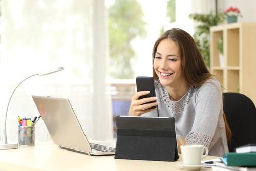 スマートフォンをみて笑顔をこぼしている女性