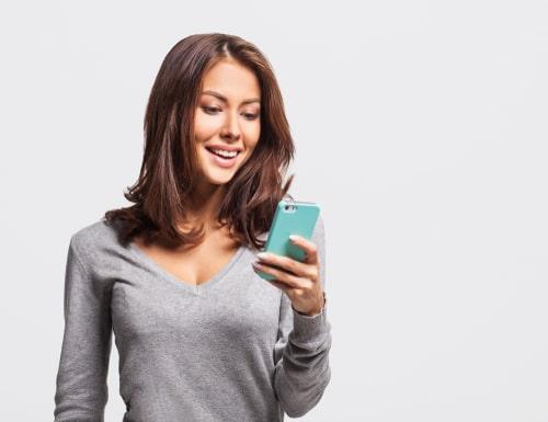 スマートフォンを見ながら微笑んでいる女性の様子