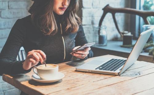 コーヒーを飲みながらスマートフォンを操作している女性